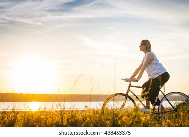 Young woman  riding bicycle along the shore at sunrise or sunset
