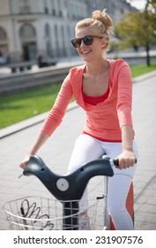 young woman riding a bicycle in the city, she has a topknot and sunglasses