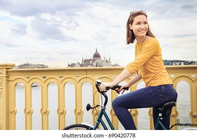 Young woman riding bicycle in city of Budapest, Hungary