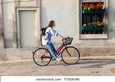 Young woman riding a bicycle down the street.