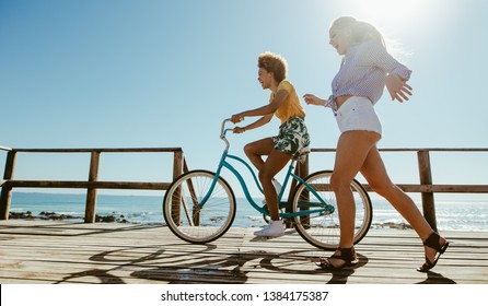 Young woman riding a bicycle with her friend running by on boardwalk. Multi-ethnic female friends having fun with a bike at the seaside boardwalk.