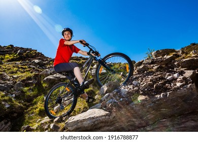 Young woman riding bicycle on country road