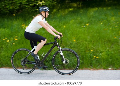 Young woman riding a bike on road through forest