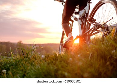Young woman riding bike over hills in sunset, view from top of the hill, legs close up