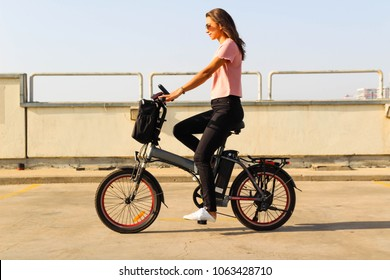 A young woman riding an electric bicycle