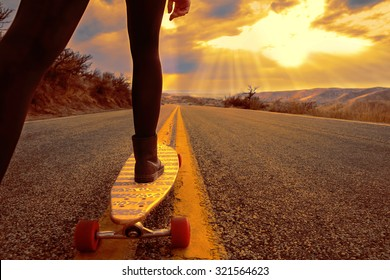 young woman riding with her longboard on a hill overlooking the city below in the valley during sunrise or sunset with a toned vintage retro instagram filter