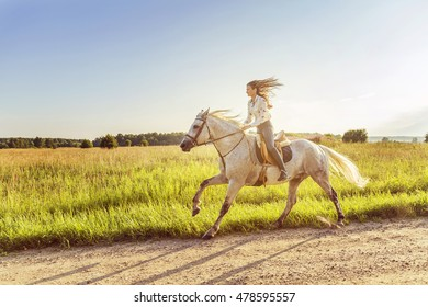 young woman riding a horse in countryside. motion, speed, freedom. selective focus