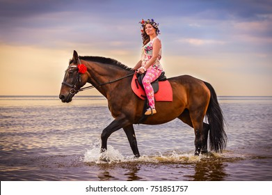 Young woman riding horse in sea at sunset. Horse on a beach. Colorful colors. Woman on horse at seashore. Seascape.