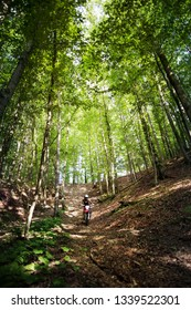 Young woman riding motocross bike downhill in a forest