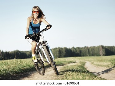 Young woman riding on a bicycle on a countryside road