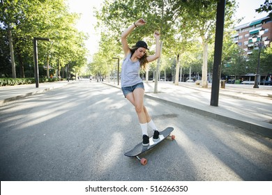 Young woman riding on her longboard.