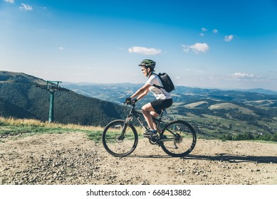Young woman riding on MTB in Carpathian mountains