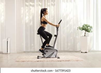 Young woman riding a stationary bike at home