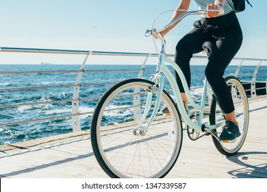 Young woman riding vintage bike along the waterfront. Female traveler with backpack cycling near sea on sunny summer day.