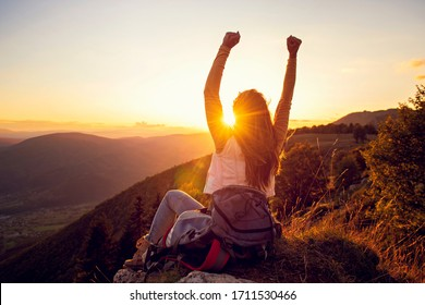 Young woman rise hand up on top of mountain and sunset sky abstract background.