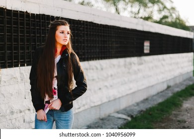 Young woman rock a black leather jacket casual stand-up cityscape background at sunset. Sexy attractive woman with a punk-rock fashion style posing against the backdrop of air ventilation. Toned photo