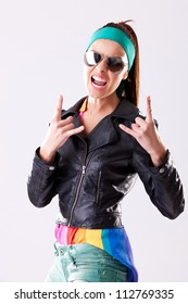 young woman rocker wearing leather jacket and sunglasses, screaming and making rock and roll hand gesture