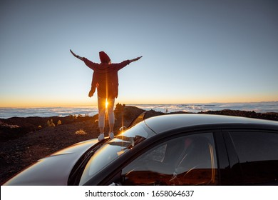 Young woman rocky landscapes above the clouds, standing on the car highly in the mountains. Carefree lifestyle and travel concept
