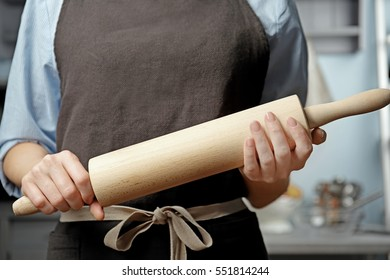 Young woman with roller pin in kitchen, closeup