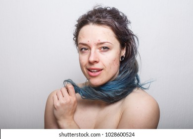 Young woman rolling her colorful but damaged messy hair on her finger. Absolutely no retouching.