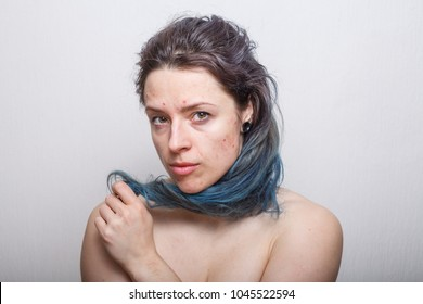 Young woman rolling her colorful damaged messy hair on her finger. Absolutely no retouching.
