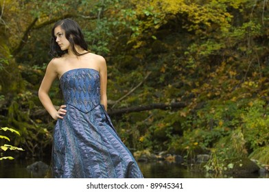 Young Woman in Romantic Woodlands near an autumn stream