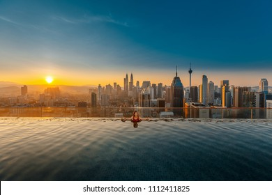 Young woman in a roof top swimming pool with beautiful city view. Vacation in Kuala lumpur, Malaysia
