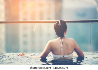Young woman in a roof top swimming pool with beautiful city view, sunlight vintage filter image