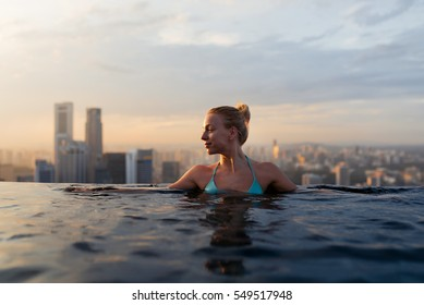 Young woman in a roof top swimming pool with beautiful city view. Vacation in Singapore