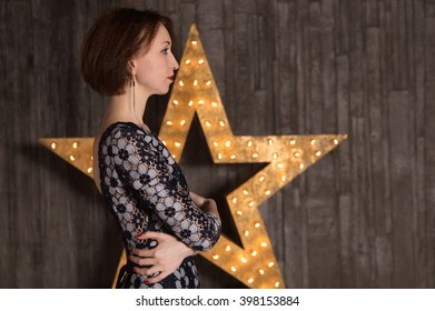 Young woman in a room on the background of stars. Concept - woman, scene, star, actor, poster.