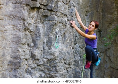 2358b54f3b5 A young woman with a rope engaged in the sports of rock climbing on the rock