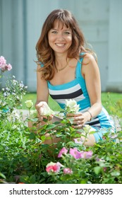 young woman in roses plant at garden