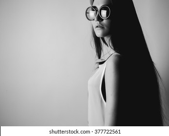 Young woman in round glasses. Black and white. High contrast