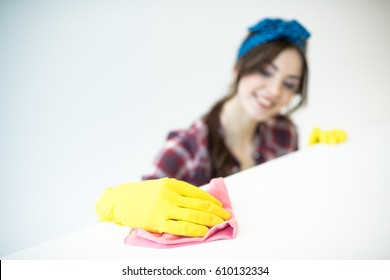 Young woman in rubber gloves cleaning surface with rag