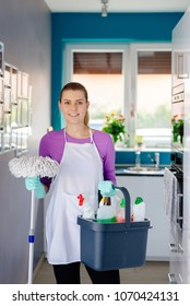 Young woman in rubber gloves holding mop and bucket with detergens. Maid cleaning at home
