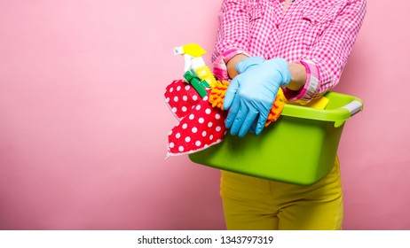 Young woman in rubber gloves holding bucket with cleaning supplies