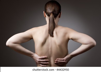 A young woman rubbing her back in pain