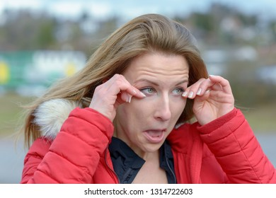 Young woman rubbing her eyes on a cold windy day
