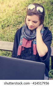 Young woman rubbing her neck while working on a laptop.