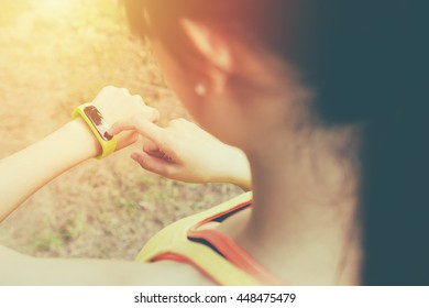 young woman run and touch wear smart watch