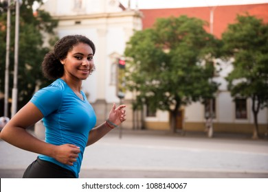 Young woman runner in action, facing camera.