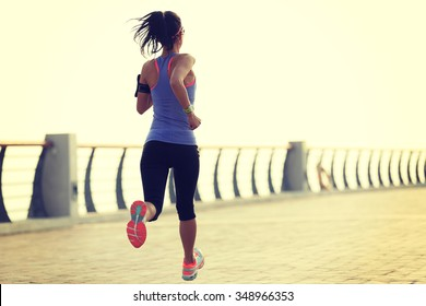 young woman runner athlete running at seaside