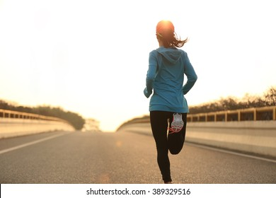 young woman runner athlete running at sunrise city road