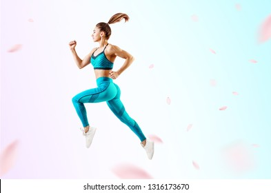 Young woman runner in blue sportswear jump in the air. Over fresh background with swirl petals
