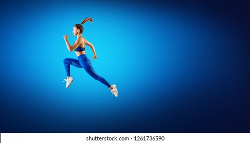 Young woman runner in blue sportwear jump in the air. Dynamic movement. Over blue background.