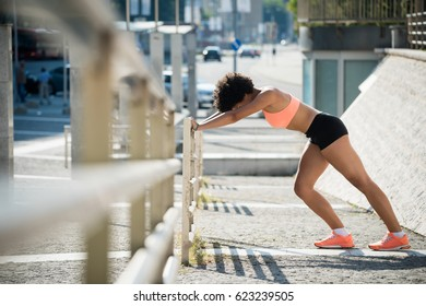 Young woman runner doing stretching exercise outdoors