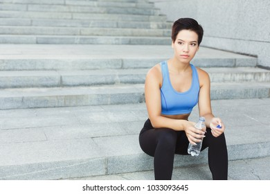 Young woman runner is having break, drinking water while jogging in city, sitting on staircase and looking away, copy space