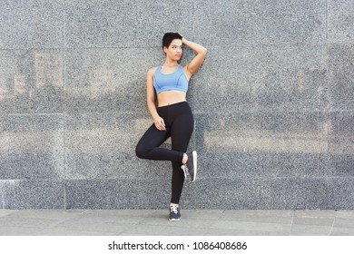 Young woman runner is having break, leaning on wall and posing, copy space. Jogging in city and healthy lifestyle concept