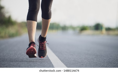 Young woman runner running on city bridge road. Young fitness woman runner athlete running on the road in the morning