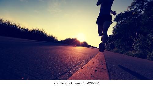 young woman runner running on sunrise seaside